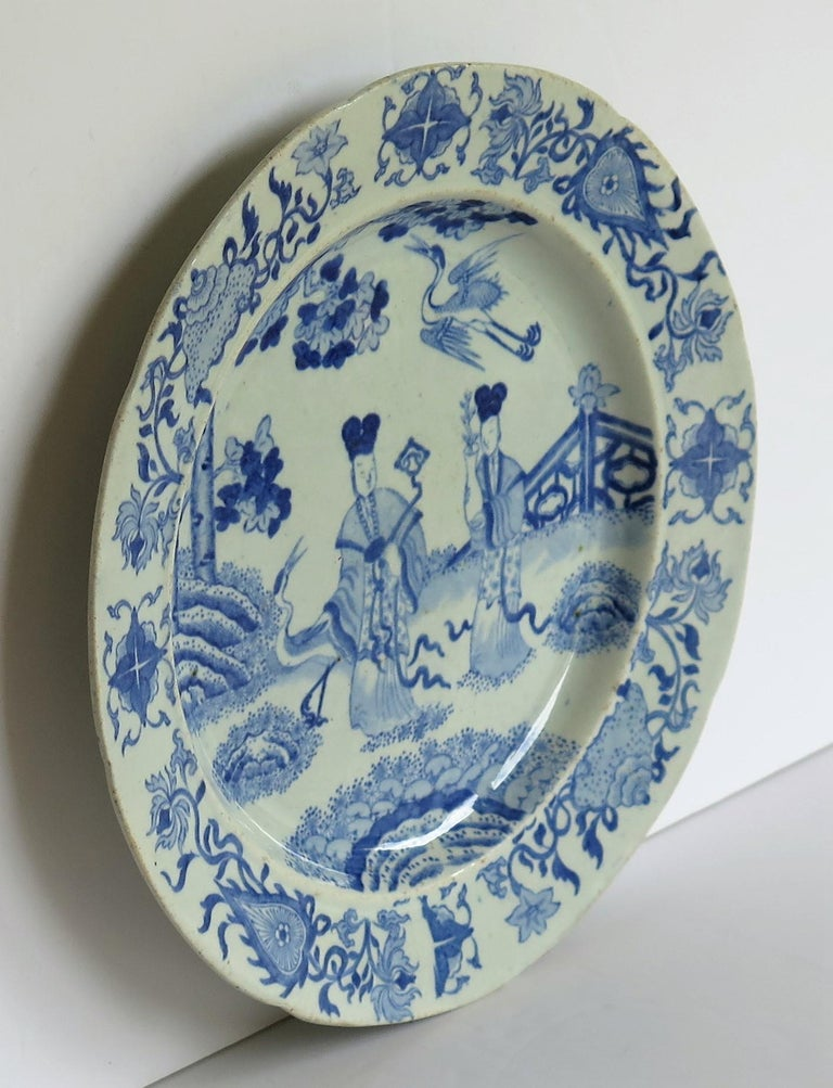 This ironstone pottery dinner plate was made by the Mason's factory at Lane Delph, Staffordshire, England and is decorated in the blue and white Chinese ladies with cranes which is a rare pattern, fully stamped and dating to the earliest period of