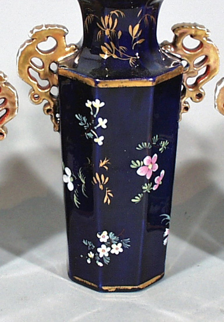 Mason's ironstone garniture of three vases, circa 1835   The three hexagonal-shaped vases are painted with polychrome flowers on a mazarine blue ground. The open-work handles, rim and feet are gilded.  Dimensions: Height 7 inches and 5 3/4