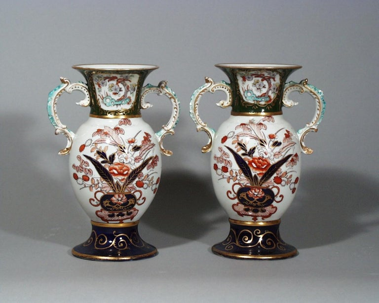Mason's ironstone Japan pattern pair of vases, circa 1830-1840.   The vases are decorated in an imari palette with scroll handles highlighted in turquoise and gilt. The circular flaring foot is in a mazarine blue ground with gilt highlights. The