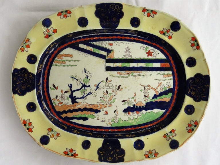This is a mid-19th century Mason's ironstone large platter in the documented colored wall pattern, made in the mid-19th century, circa 1840.   This large meat platter is decorated in a very bold chinoiserie pattern called the colored Wall pattern