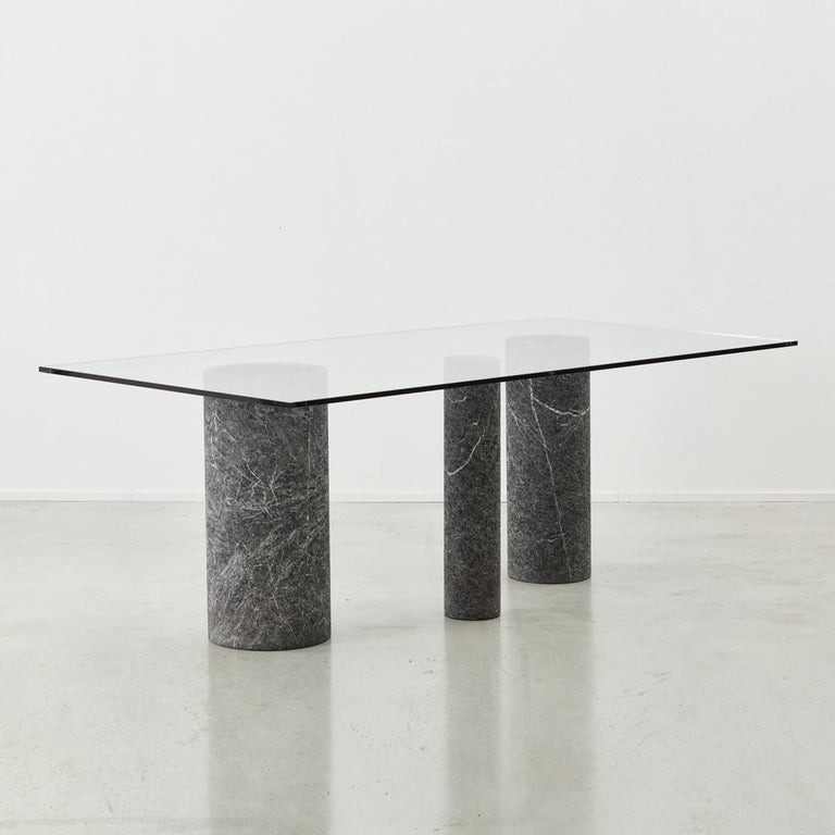 This striking dining table by Massimo Vignelli for Italian producer Casigliani is made from marble columns and glass. The three marble columns each vary in diameter, their facades systematically chipped to create a rough yet tactile surface texture.