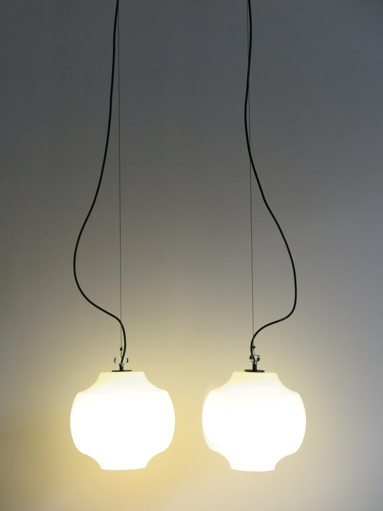 Italian Mid-Century Modern design set of two pendant lamps designed by Massimo Vignelli and produced by Venini with Murano glasses and details in lacquered metal, 1960s  Please note that the lamps are original of the period and this shows normal