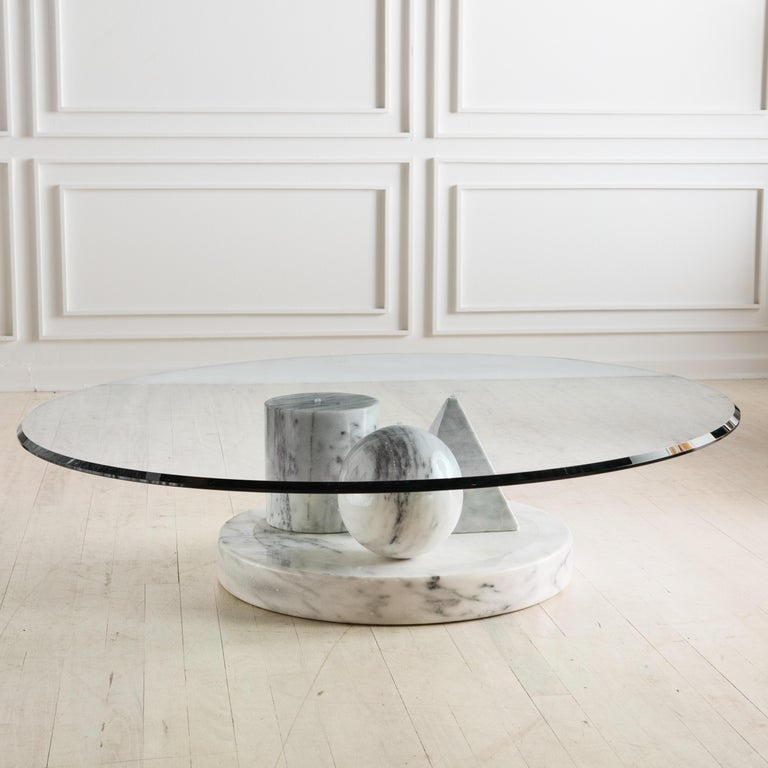 """A dynamic use of marble and shapes, this Italian coffee table was designed by Massimo Vignelli for Casigliani. This features a marble triangle, sphere and cone all situated on a 23"""" thick and 23"""" diameter marble base on which a thick clear glass top"""