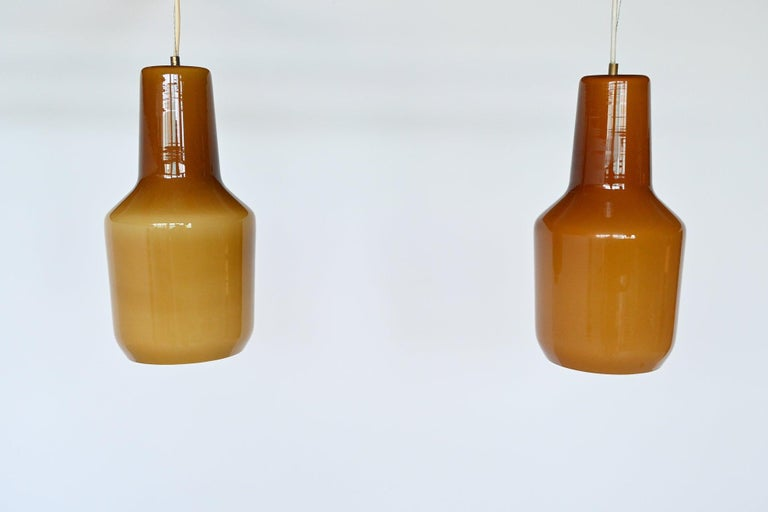 Beautiful pair of pendant lamps designed by Massimo Vignelli and manufactured by Venini, Italy, 1960. These lamps are made of hand blown thick clear brown colored glass with a white inside. That makes sure that these lights give a nice and warm