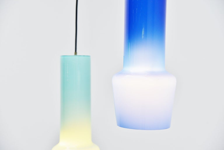Fantastic pair of pendant lamps designed by Massimo Vignelli and manufactured by Venini, Italy, 1960. The lamps have a nice light and dark blue color. Because of the white inner glass they have a nice and deep color. The lamp have a brass fixture on