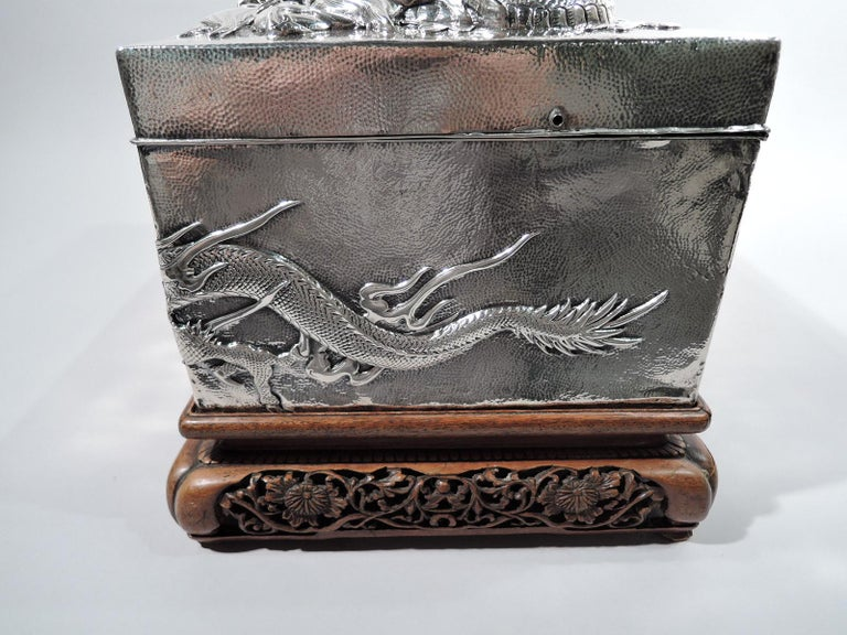 Massive Japanese silver casket box, circa 1890. Rectangular with straight sides and hinged cover with loose-mounted trefoil handle. All-over spot hammering. Applied to sides are two wraparound dragons-scaly and slithering beasts with major