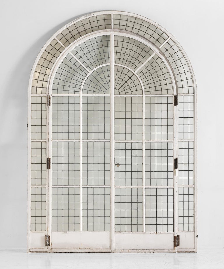 Massive arched doorway, England circa 1900.  Painted metal framed glazed doors. The glass is fixed with a mixture of copper and lead.