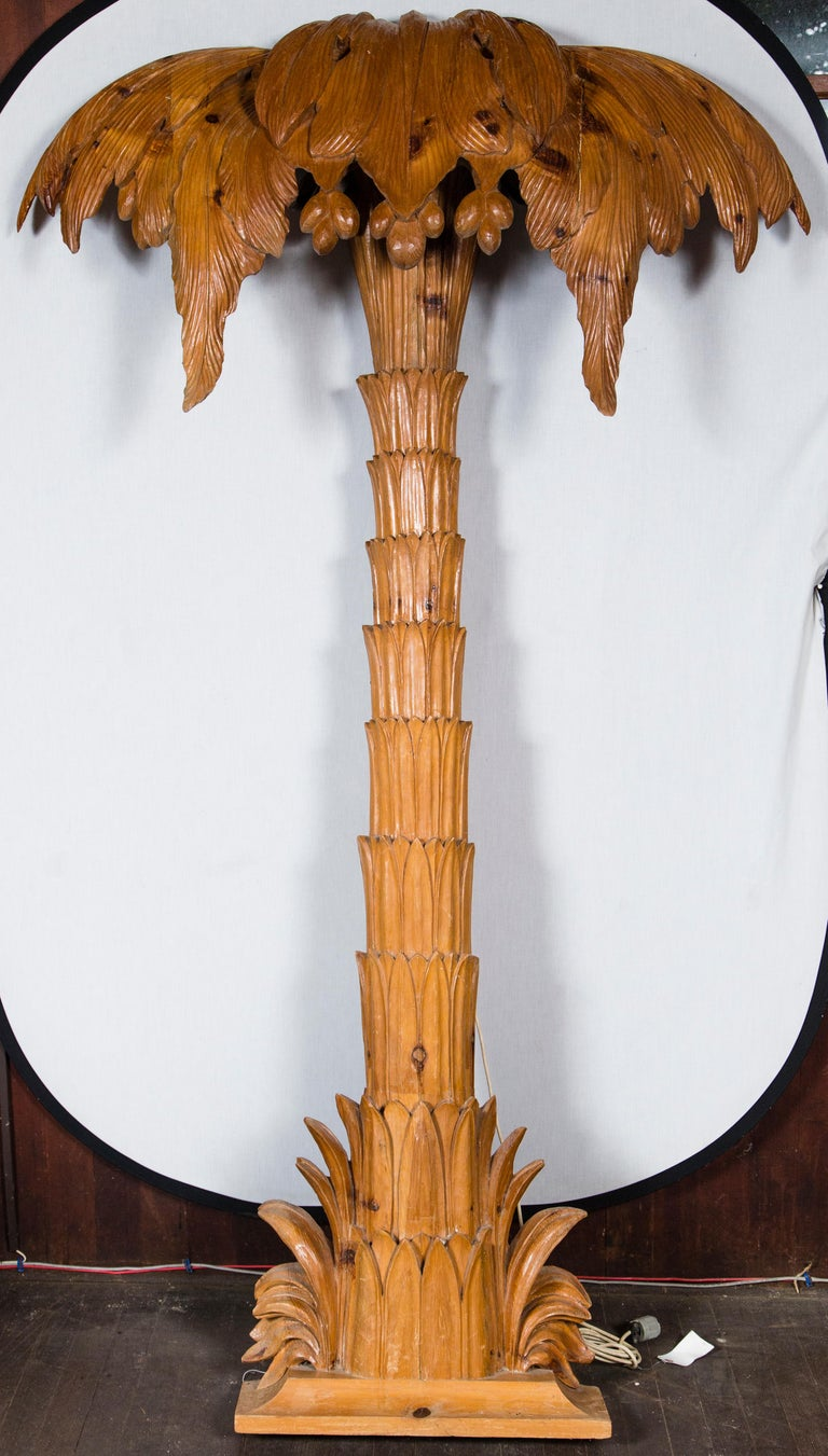 A grand carved pilaster style wood palm tree with tiny lights.