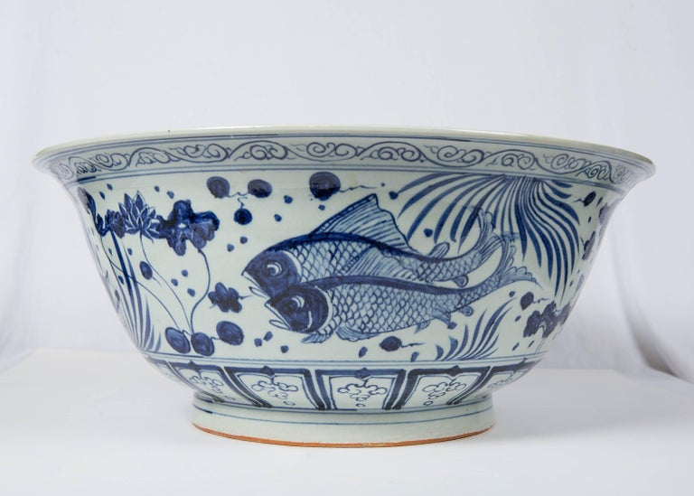 We are pleased to offer this massive hand painted Chinese blue and white punch bowl with decoration based on the popular fish-and-aquatic plants motif. This motif was frequently painted on blue and white porcelain beginning in the Yuan-era