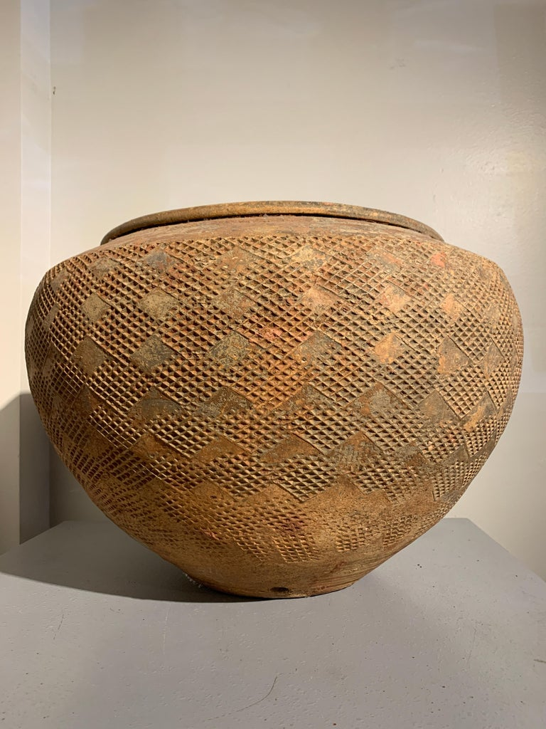 A stunning and massive Chinese high fired gray pottery jar of remarkable size and girth, with impressed geometric design, Eastern Han Dynasty (25-220 AD), Zhejiang Province, China.  The coil-formed massive high fired gray pottery storage jar of