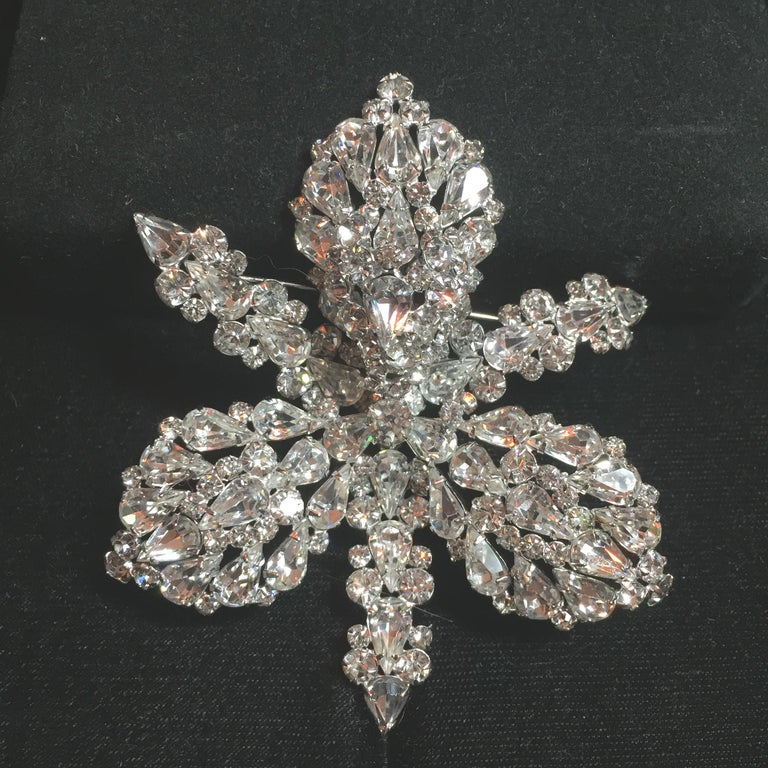 Offered here is a massive Elsa Schiaparelli rhodium-plated brooch and matching clip-back earrings from the 1950s. The exquisitely engineered hand-soldered three-dimensional design is that of a three-lobed orchid blossom hand-set with hundreds of
