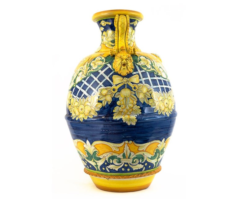 This massive Italian urn/jar/vase has spectacular hand painting in vibrant yellows and rich golds on a dark blue background. At almost 40