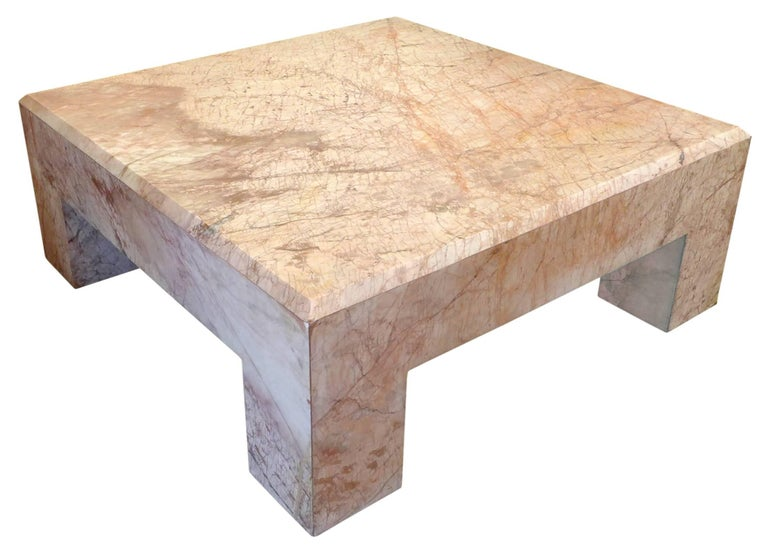 A beautiful and massive rose marble coffee table. A monumental, reduced form of incredible scale and impressive, architectural presence. An alluring, figured, multi-toned surface with a beveled perimeter. A spectacularly-decorative, utilitarian item