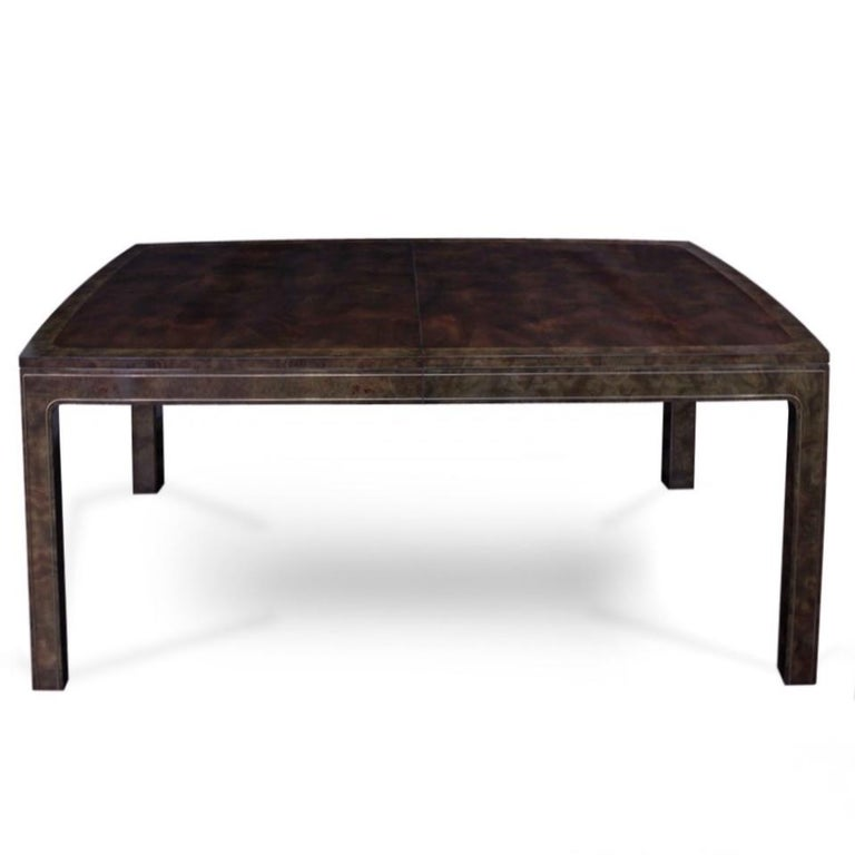 Designed by William Doezema, this refined model 869 dining table by Mastercraft features burl amboyna wood with brass trim details. With the installation of three 20