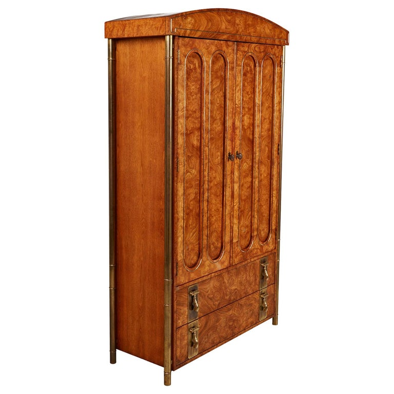 Breathtaking burl wood and brass Mastercraft armoire. Four tubular outer skeletal brass support legs create a floating effect. The columns are fashioned in the style of bamboo stalks to add an Eastern flare. Hollywood Regency and Asian Modern meld