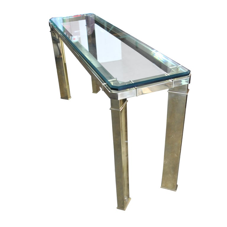 A mid century modern console or sofa table made by Master Craft.  A brass frame with angled legs and beveled glass top.