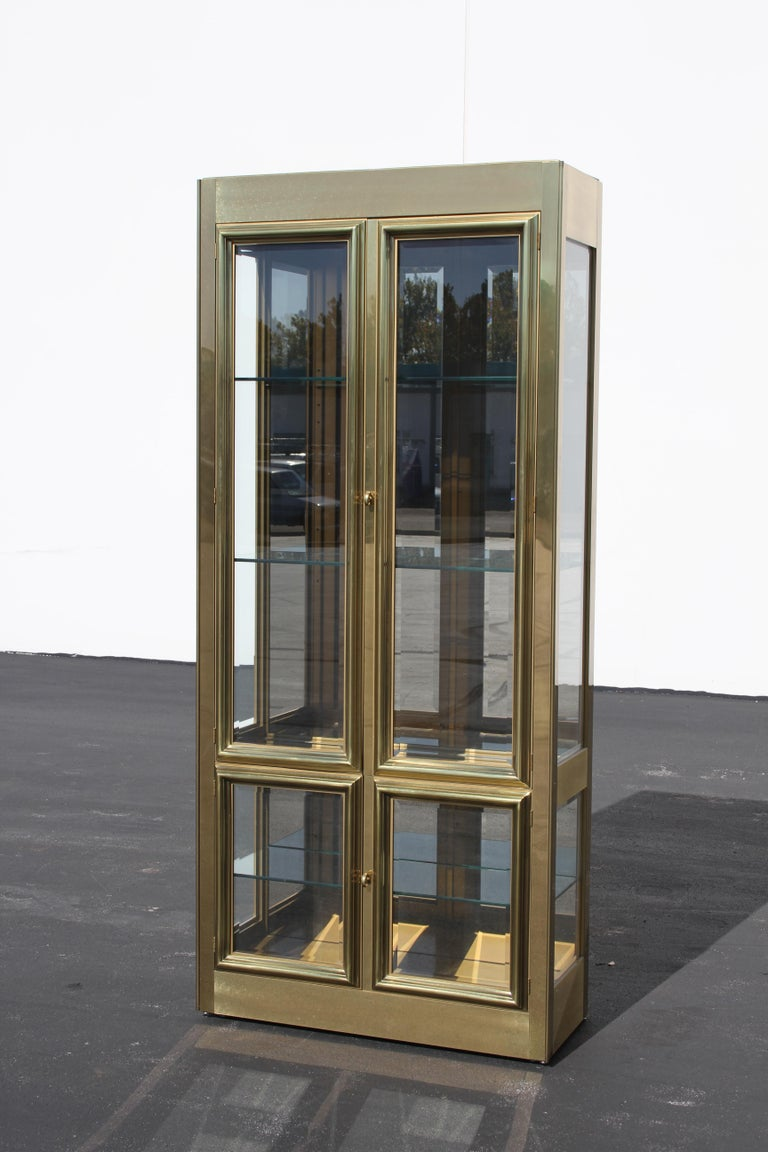 Mastercraft brass display or Vitrine with four beveled glass doors, design is circa 1970s, this was manufactured in the 1980s. Has three adjustable glass shelves and mirrored backing. Ceiling has two internal lights, switch and cord. Upper case with