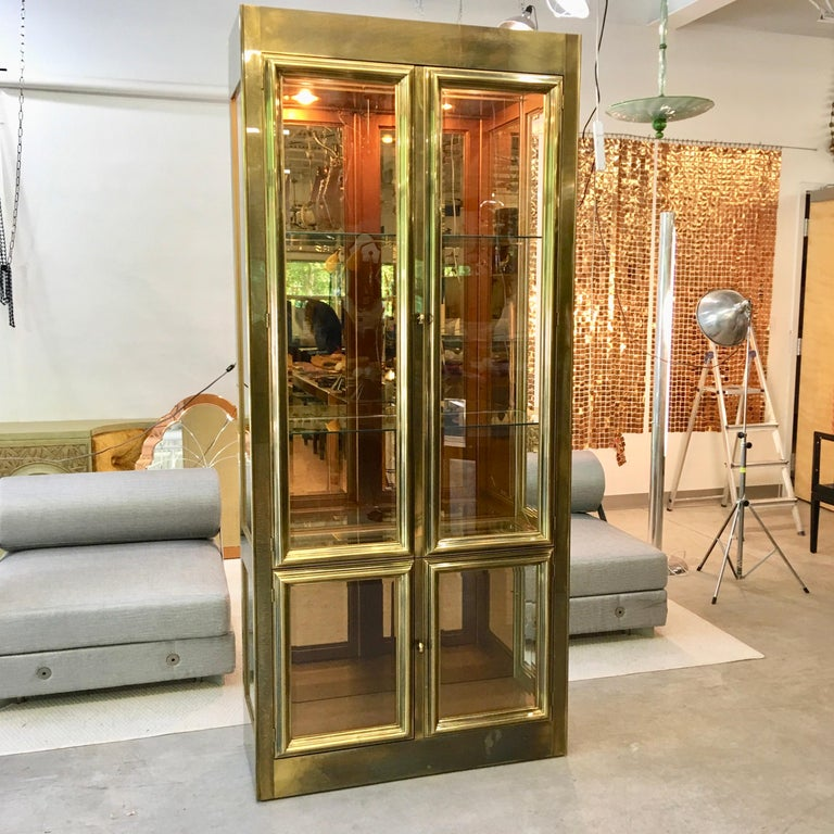 Four door brass vitrine display case by Mastercraft of Grand Rapids, Michigan circa 1970. Upper case with two tall doors; lower case with two short doors; all doors with beveled glass framed in heavy brass moulding. Upper and lower sidelight windows