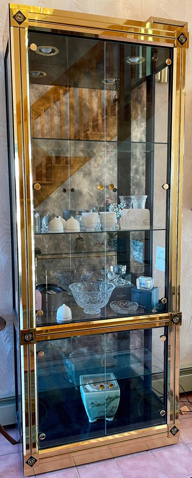 Uncommonly seen Model 280 polished brass vitrine china display cabinet, designed by William Doezema and executed by Mastercraft of Grand Rapids circa 1970,  Four glass doors, three adjustable glass shelves with groove for plate or picture display