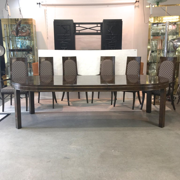 Vintage 1960s dining table and six chairs designed by William Doezema for Mastercraft retailed by Charak of Boston. Briar root burl veneer although frequently identified as Amboyna. Brass trim all along apron up and around legs. Table when closed is
