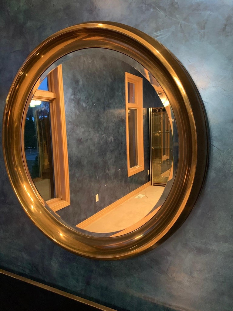 Oversize vintage 1970's mirror by William Doezema for Mastercraft in a wide rimmed patinated brass moulded frame featuring an inset circular beveled mirror.