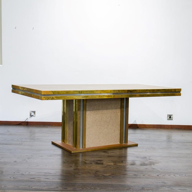 A brass and leather dining table designed by Mastercraft with aluminium strips breaking up the brass, 1970s.  Mastercraft is synonymous with high style and high society living from mid to late 20th century. The American based company created
