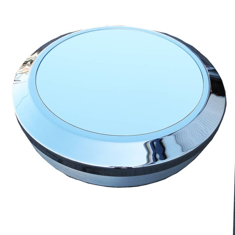 "One of the most forward designs ever produced from Mastercraft was this ""flying saucer"" coffee table. The body is a turned and brushed aluminum, capped by a chrome-plated ring. The top surface is an newly replaced inset circular mirror. The iconic"
