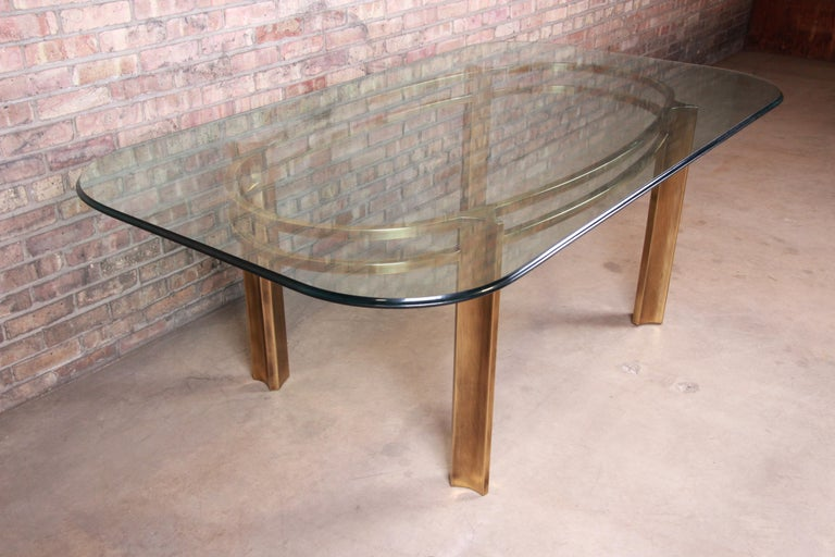 An exceptional midcentury Hollywood Regency dining table  Produced by Mastercraft for Baker Furniture  USA, 1970s  Brass base with thick beveled glass top.  Measures: 80