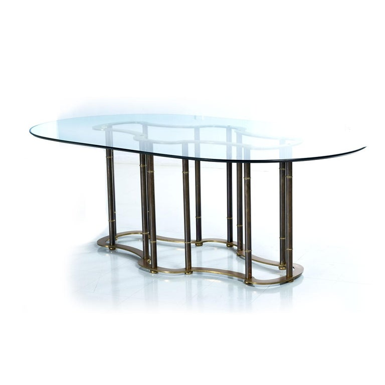 This expertly embodied faux bamboo brass dining table proudly wears its over four decade old patina. The patina gives the otherwise gold colored brass a dark, black bamboo look. The top of the table pedestal resembles a racetrack. The undulating