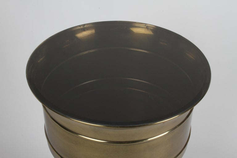 Hollywood Regency Brass Mastercraft cylindrical display pedestal with smoke glass top. The glass top is removal, and then can be used as a Jardiniere, see images. In fine condition, great original patina to brass. Inside planter dims. Measures: 15