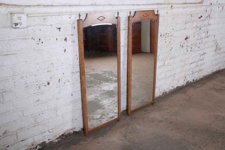 A gorgeous pair of Mid-Century Modern Hollywood Regency wall mirrors  In the manner of Mastercraft Furniture  USA, 1960s  Burled Carpathian elm + brass + mirror  Measures: 20.5