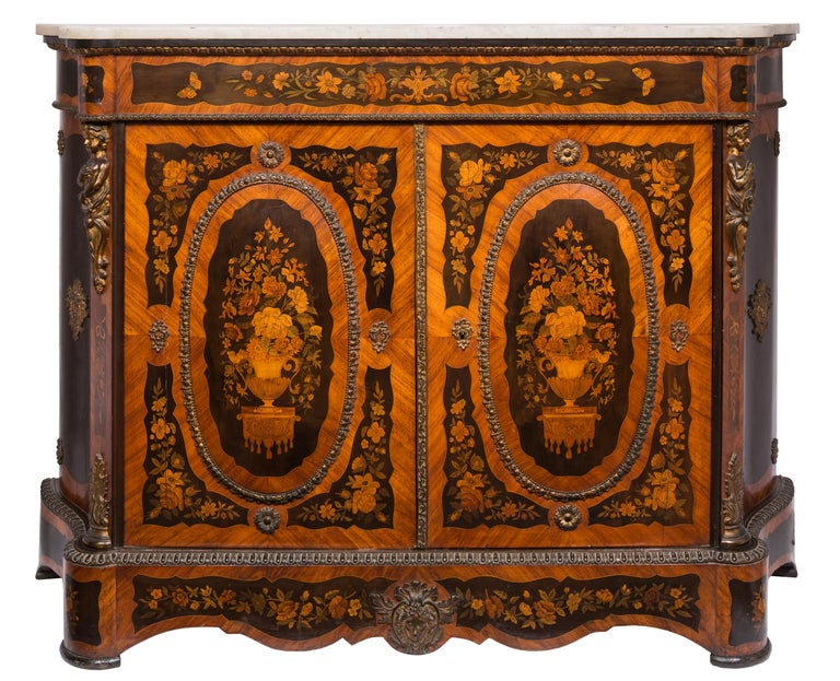 A matched pair of 19th century French Louis XVI style double door side cabinets with intricate multi-wood floral motif marquetry and gilt-bronze details. The central oval image area of each door is slightly convex, and the sides of the cabinets are
