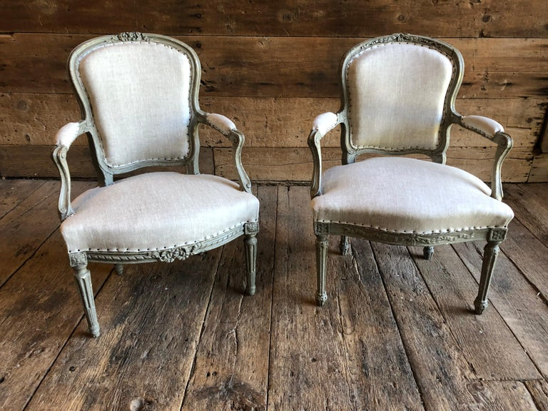 A matched companion pair of transitional Louis XVI period fauteuils in old grey painted finish, the arms showing elements of the early Louis XV period with subtle curves and scrolls, the back and seat rail with floral and ribbon carvings, both on