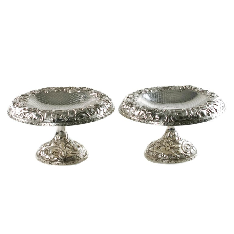 This unusual matched pair of sterling silver tazzas were made by the Baltimore Silversmiths Manufacturing Company, founded in 1903 by Frank M. Schofield. The tazzas have been finished in the elegant Castle Landscape pattern and feature ornate