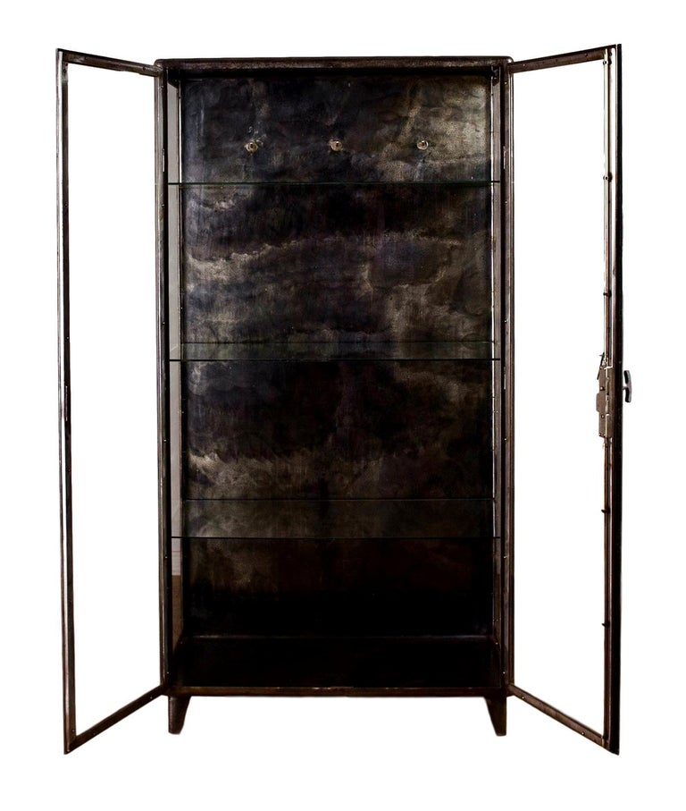 Stunning Art Deco vitrine made in the 1930s in Belgium. Great original patina to metal. Glass doors and sides. Metal back. All glass in great shape. Working doors and handle with original lock and key. 4 glass shelves. Great display cabinet. Only