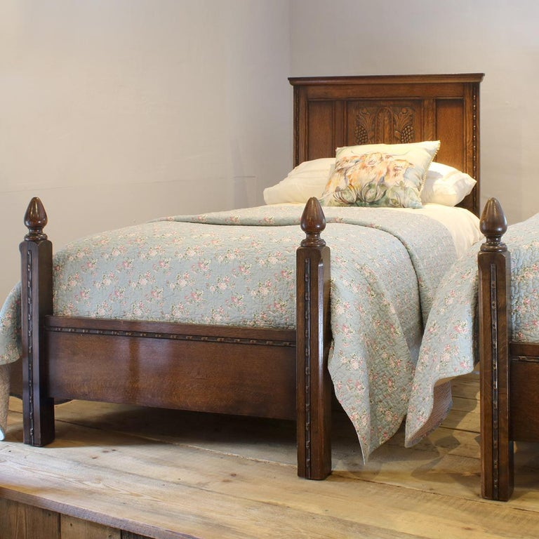 Matching pair of oak early 20th century beds with carved paneled backboards and torchon feet.