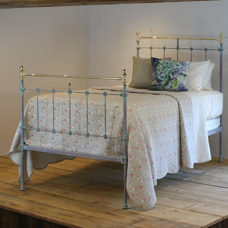 A matching pair of twin brass and iron beds finished in blue verdigris with straight brass top rails, egg-shaped cast brass knobs and decorative daisy-shaped castings.  These beds accept 3ft 6in wide (42 inch or 107 cm) bases and