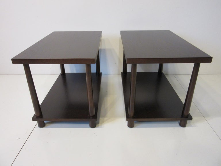 A matching pair of very well crafted double platform end tables / nightstands or side tables with reversed tapered legs in a rich medium ebony toned finish . Retains the manufactures label to the bottom of the table tops by the Widdicomb Furniture