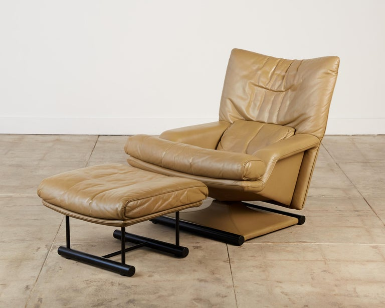 Lounge chair and ottoman designed by Mathias Hoffmann for Rolf Benz, Germany, c.1980s. The set was made for US export to be sold by American retailer Cy Mann. It features a fully upholstered tan leather body and base with two black painted metal