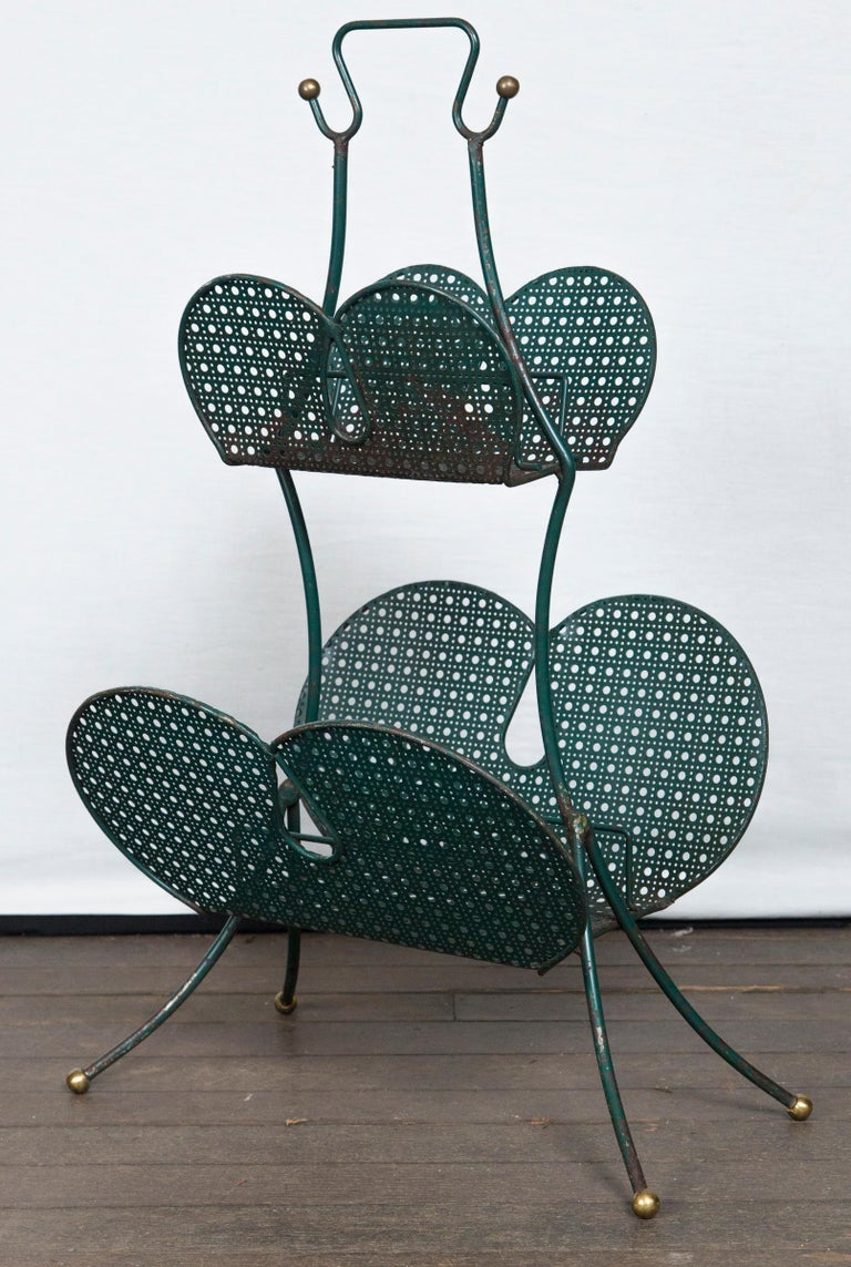 A French Matégot metal magazine rack which is both modern and whimsical from the 1950, perforated metal, metal, and brass.