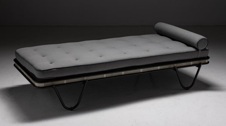 Mathieu Matégot Daybed, France 1950.  Newly reupholstered in Mahaham worsted wool charcoal grey with black trim. Pierced metal frame painted black and white.  Measures: 77