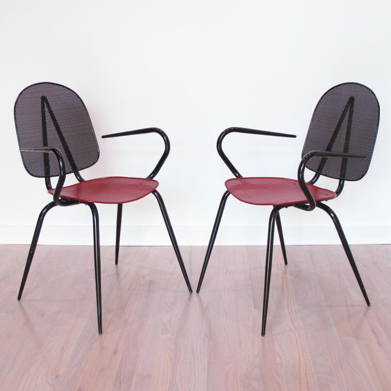 Stunning pair of metal chairs or armchairs, design in the manner of Mathieu Mategot. A striking example of French 1950s metalwork. Folded and perforated black and red lacquered metal. Great modernist shape and very comfortable. Perfect for any