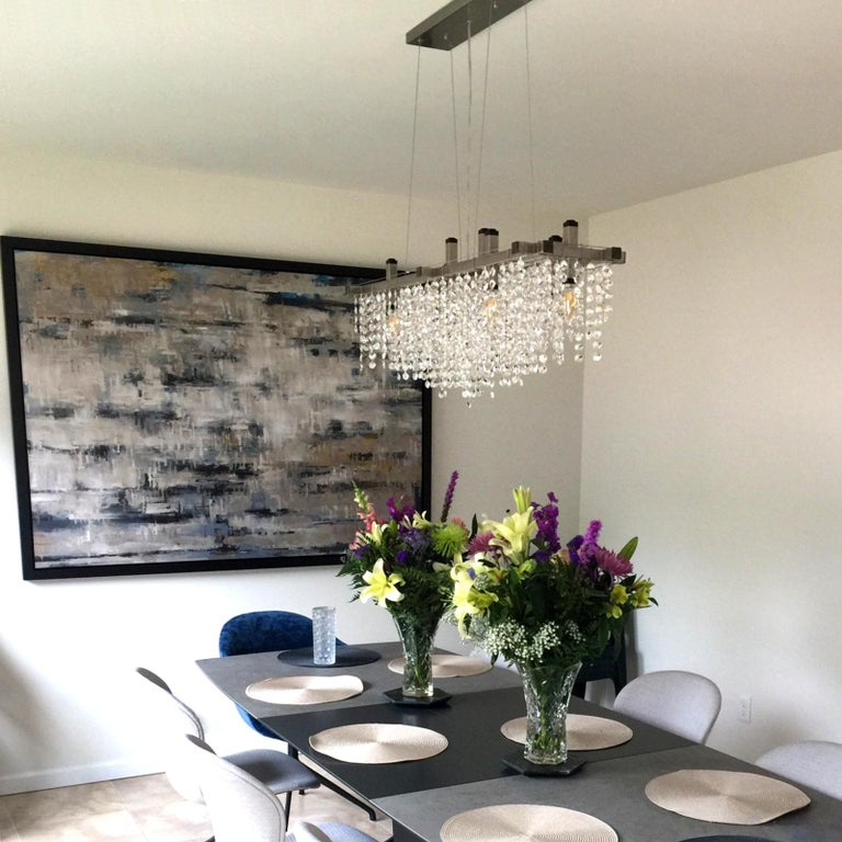 The matrix crystal linear suspension chandelier is a figurative shower of light, refraction, and highly-polished crystal. Random chains of high-quality crystal octagons and squares hang from a taut steel cable grid to create the appearance of