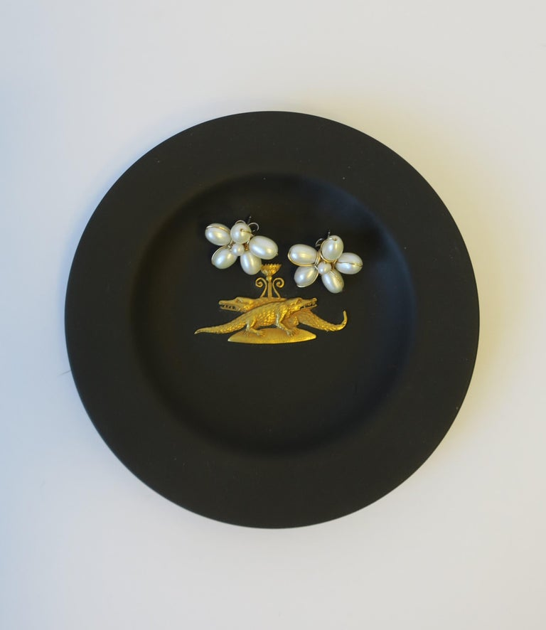 A chic and rare English Jasperware matte black basalt and gold dish by Wedgwood, England. A very beautiful small dish, with a gold raised relief of two alligators or crocodiles. Dish is beautiful as a standalone piece, or for small jewelry or other