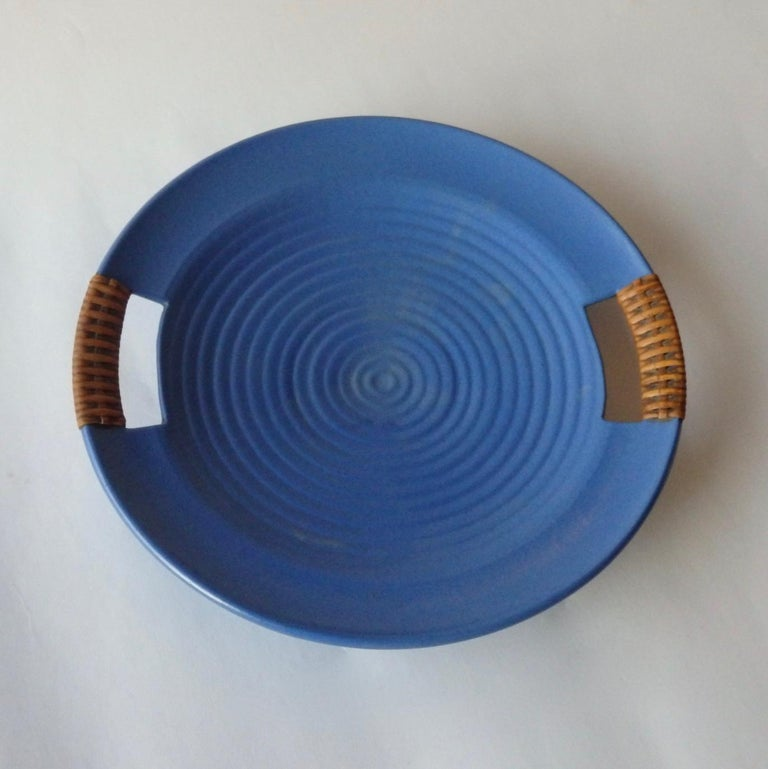 Matte blue glaze California modern serving tray. Concentric ring design . Retains Telmarck paper label and original cane wrapped handles . I am not sure if Telmarck was a retailer or the pottery . The tray does echo the work of Bauer in California .