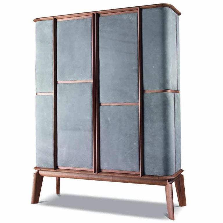 Solid walnut wood makes the structure of this cabinet that is a functional piece of design. The slanted legs evoke the charm of midcentury Furniture, while precious panels of grey-colored nubuck leather upholstery the sides and front to add elegance