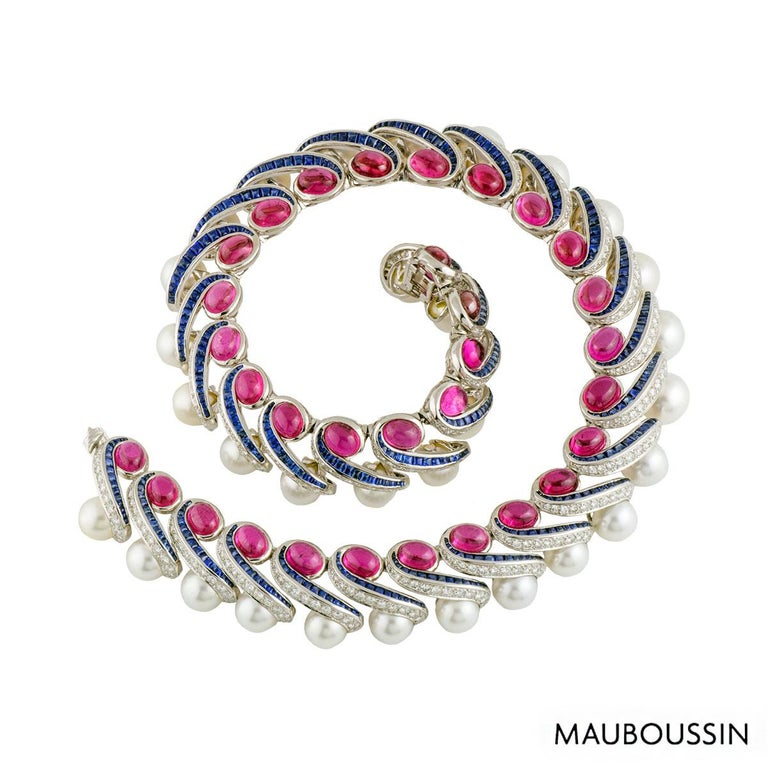 A magnificent 18k white gold multi-gemstone necklace. The necklace is of a choker style comprising of 32 waved links each featuring a round cabachon cut pink tourmaline with 2 rows trailing down vertically finished off with a pearl. One trail is set
