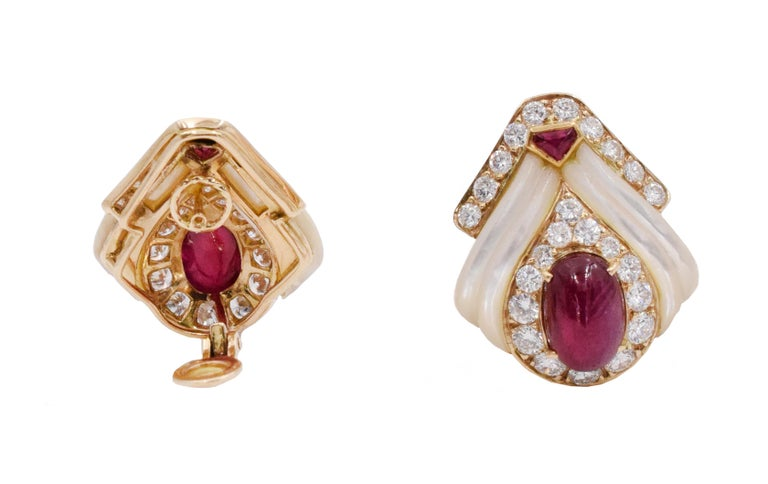 Mauboussin Paris ruby, mother of pearl and diamond ear clip earrings. .Consisting of two oval shape cabochon cut rubies in the center, and two smaller cabochon cut rubies on the top of the earrings. Accented by 50 round brilliant cut diamonds