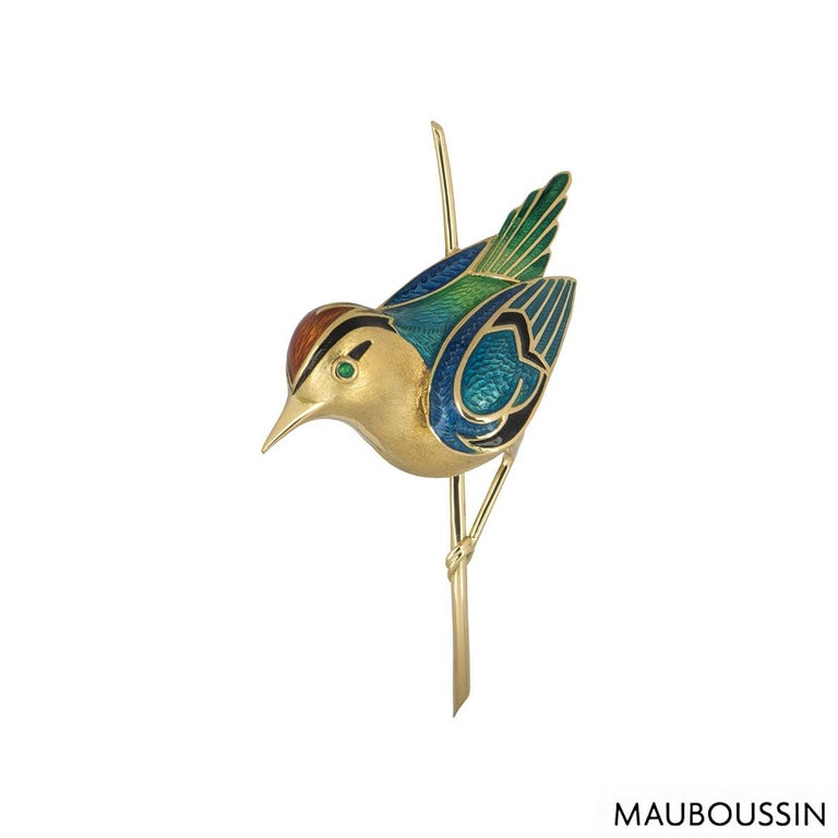 An 18k yellow gold bird brooch by Maboussin. The bird brooch is partially set with polychrome guilloché enamel on the wings and body of the bird with a coloured stone eye. The brooch is fitted with a trombone clasp with a height 5.60cm, length of
