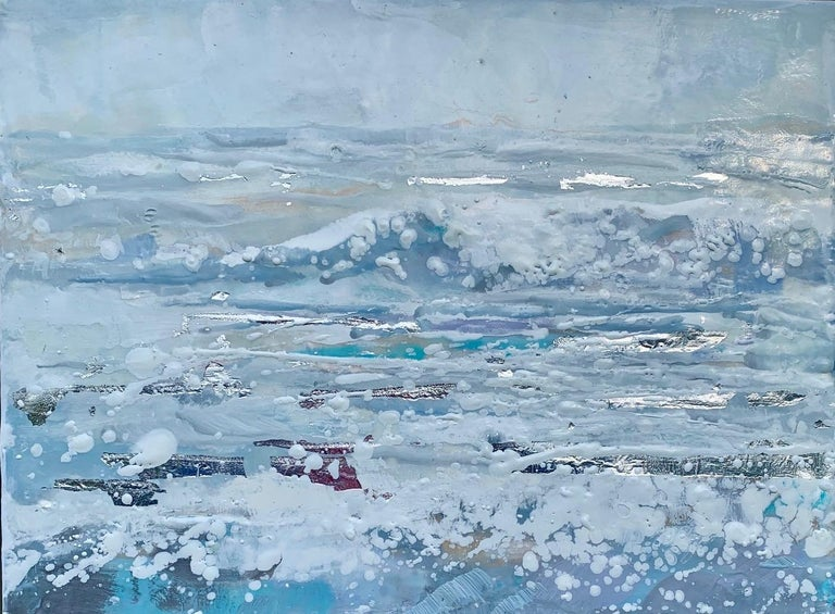 'Salt Air' is a small silver framed encaustic on board seascape painting created by American artist Maureen Naughton in 2019. Featuring a delicate palette made of grey, soft blue, purple and white tones, the painting depicts foamy waves crashing